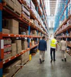 Three people in the middle of an aisle of warehouse looking at equipment handling solutions and material handling equipment